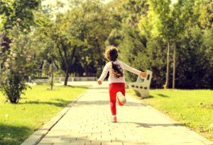 Little girl running through park