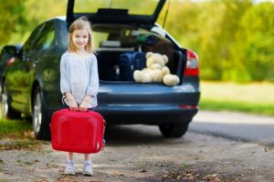 Little girl holding suitcase